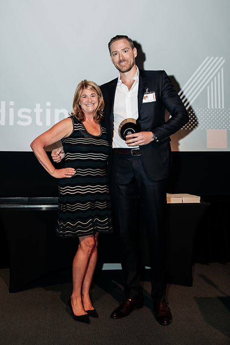 A smiling woman poses with a smiling man on stage after she presents an award to him on stage