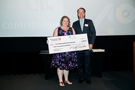 A smiling representative from San Diego Habitat for Humanity is on stage accepting a check for $5,000 from Design Institute of San Diego's CFO Dennis Doucette