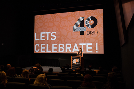 A woman named Margot Doucette is standing on stage at a podium addressing an auditorium of guests for the 40th anniversary celebration