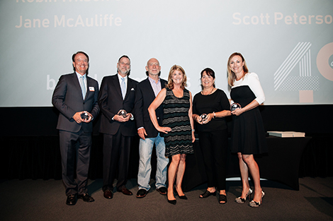 Six board members from Design Institute of San Diego, three men and three women, are posing and smiling on stage during the awards ceremony