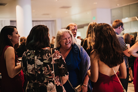 A photo of a smiling woman surrounded by other women, having a conversation