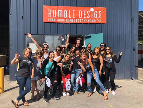 A team of DI and Humble Design volunteers pose in from of the Humble Design warehouse