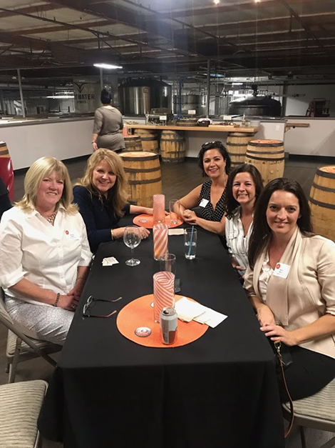 Five women including 4 alumna and the school's financial aid director, pose for a photo at their table