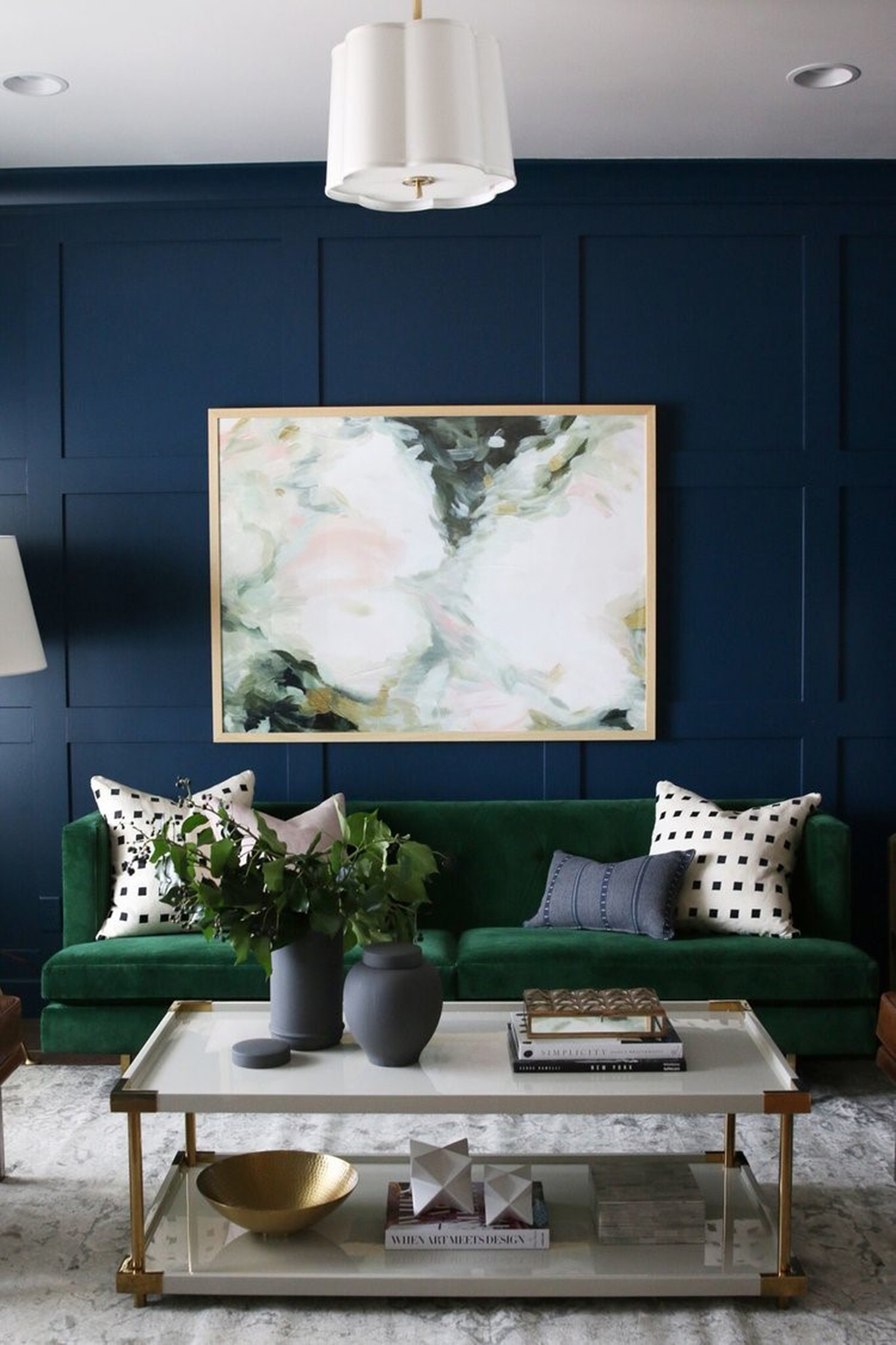 Go bold, or go home. Love this forest green velvet sofa against that regal royal blue wall.