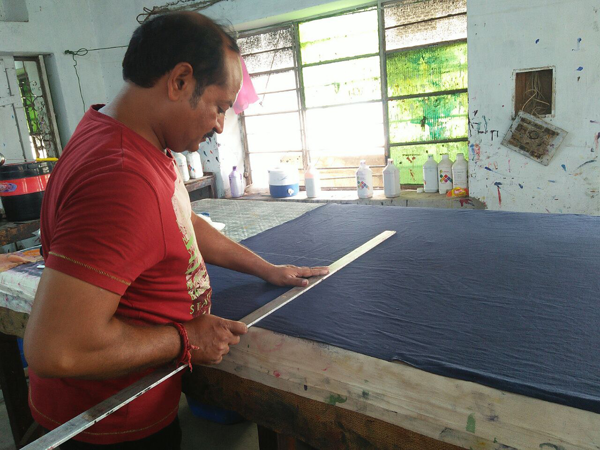 Textiles studio worker measuring and cutting Chelsea's fabric for pillow cases