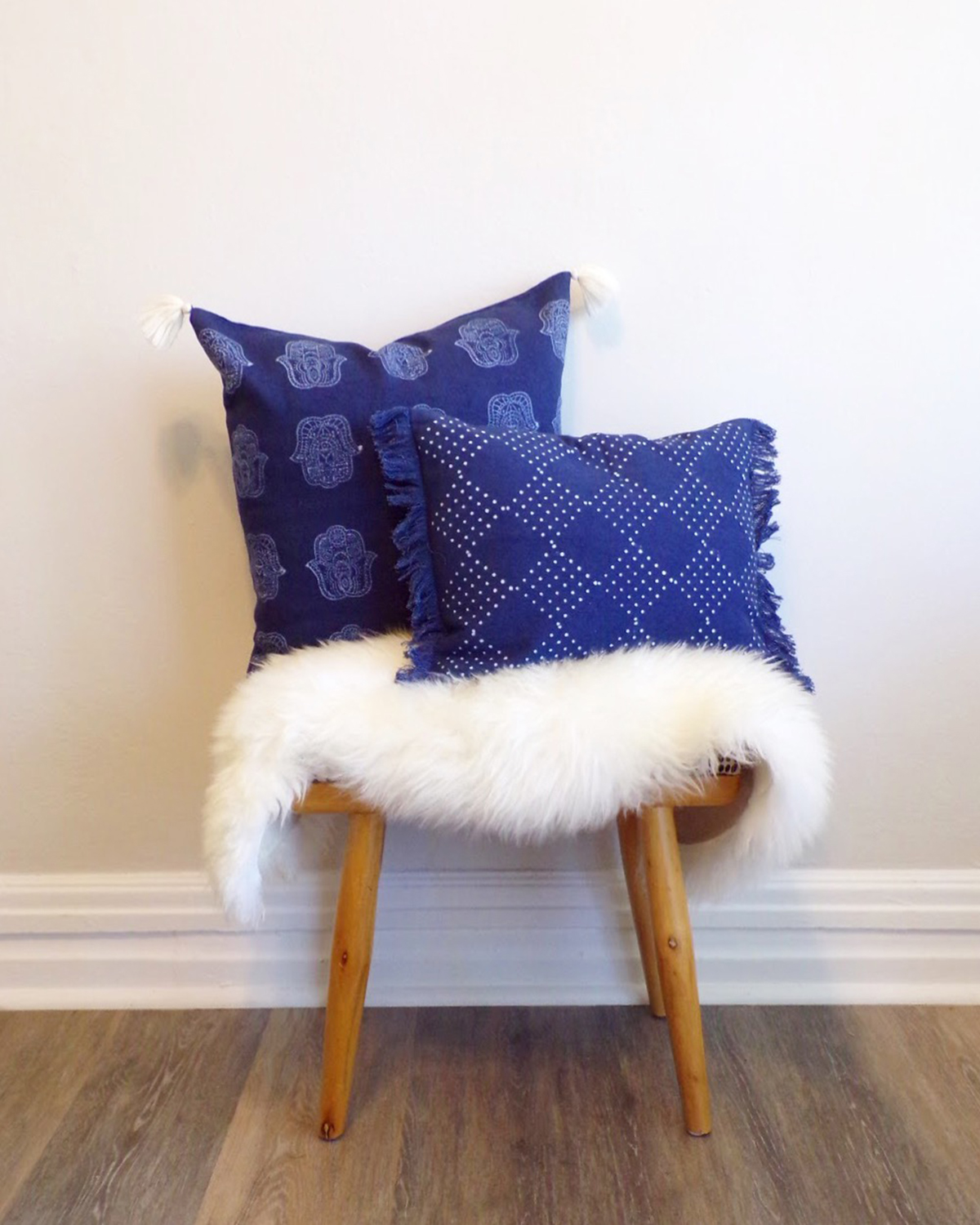 Shot of two pillows with blue pillow cases sitting on a throw and stool. Pillows are covered with Chelsea's design
