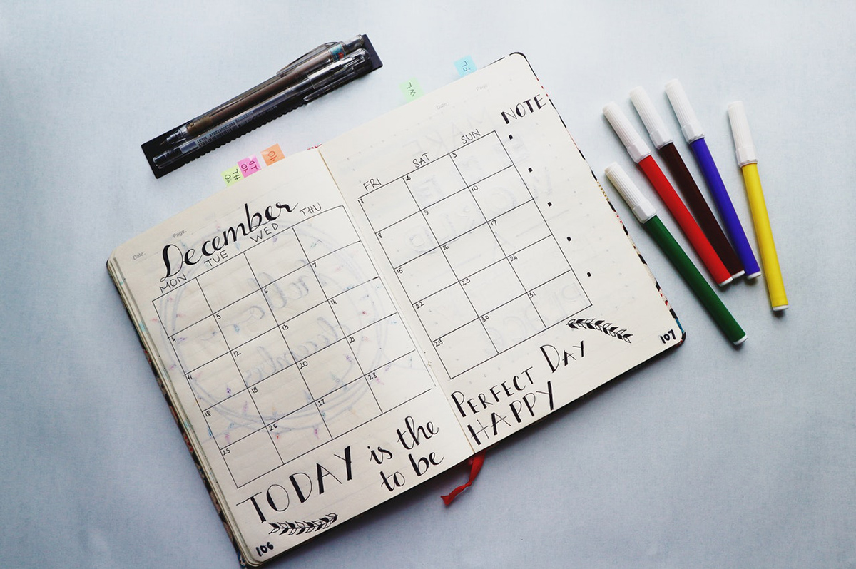 A day planner on a table, opened to the month of December, with a few markers laying around it
