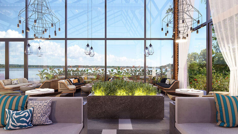 Interior Design Trends 2020 - Anxiety Relieving Space. Image shows a beautiful, tranquil interior space with floor to ceiling windows covering the walls. There is a garden block in the center of a room with plants growing, and surrounding the garden block are various seating options