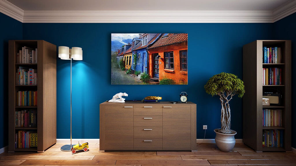 Interior Design Trends 2020 - Bold Colors. A stylized shot of an interior space, showing royal blue painted walls, with a brown credenza in the center. There is a photo of houses hanging above the credenza