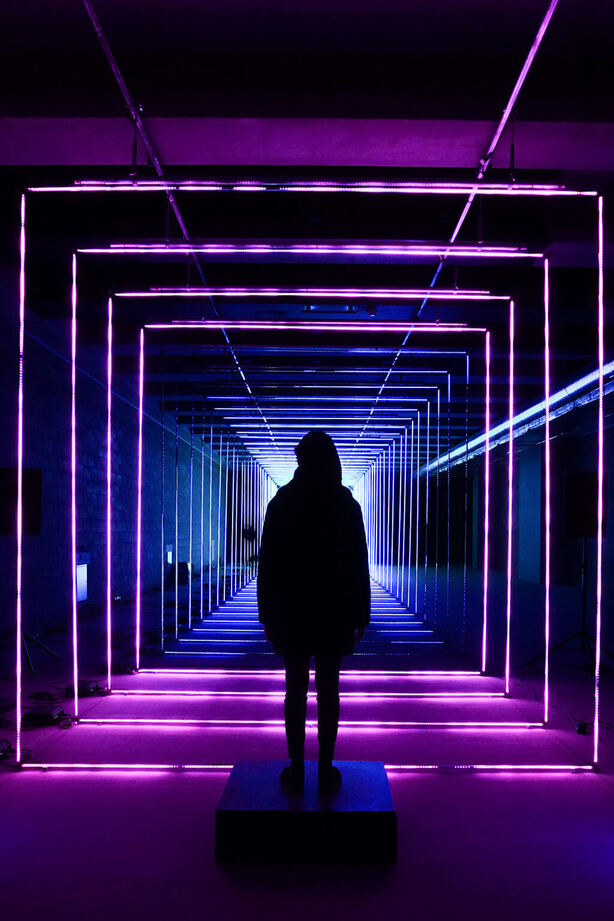 Escapism. There is a person standing at the end of a hallway with fluorescent purple neon lights shaped as a squares and framing the hallway