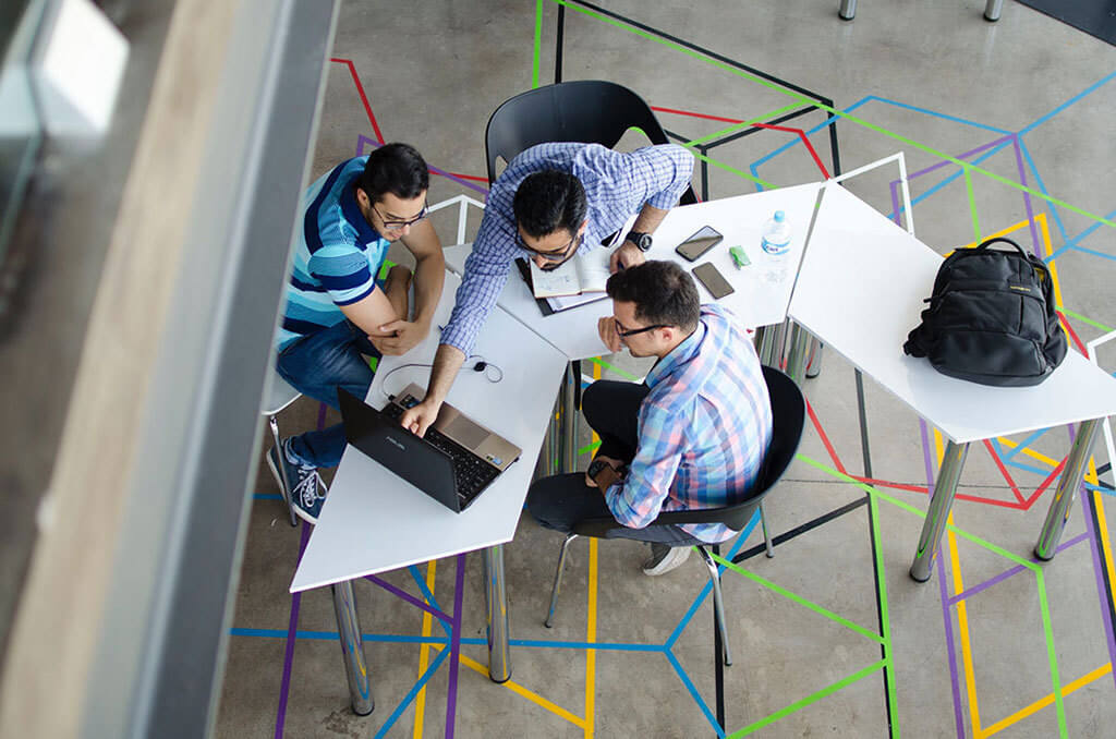 Interior Design Trends 2020 - Shift from Private to Shared Space. A bird's eye view of three people huddled at a table, looking at a laptop.