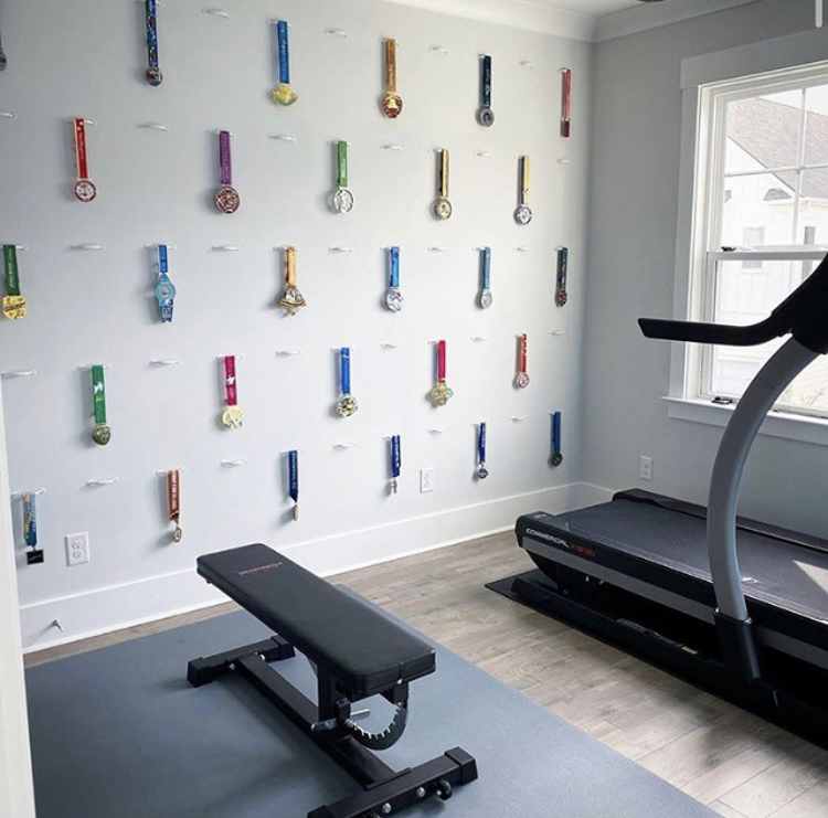 An in-home gym with a flat bench and a treadmill. On the wall behind the equipment, awards and medals hand on hooks.